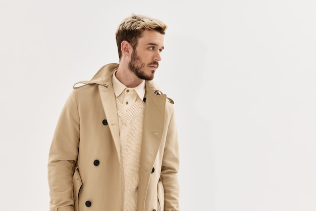 Knappe man in beige jas modieuze kapsel kant blik lichte achtergrond