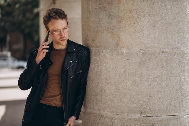 Knappe man in bril met behulp van de telefoon