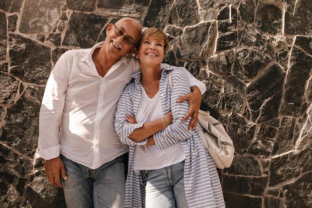 Knappe man in brillen, shirt met lange mouwen en spijkerbroek knuffelen met lachende dame met kort kapsel in gestreepte blauwe blouse