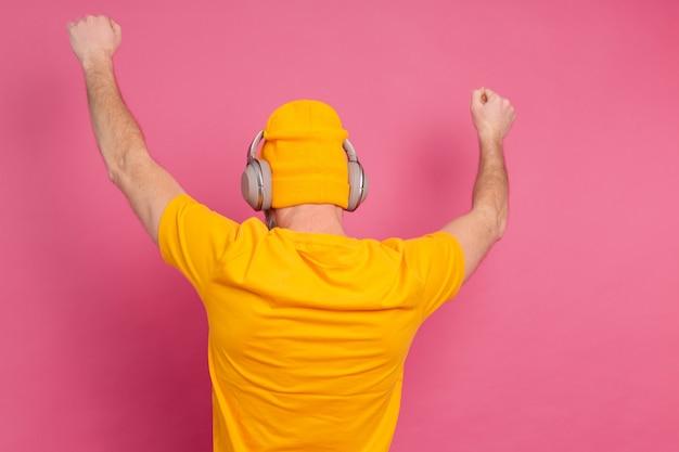 Knappe man in casual dansen met koptelefoon geïsoleerd op roze achtergrond