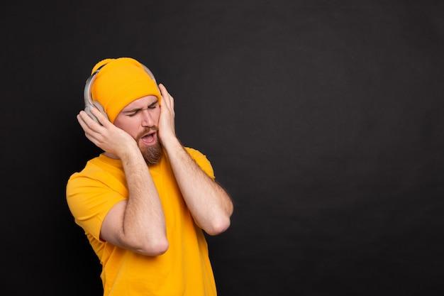 Knappe man in casual dansen met koptelefoon geïsoleerd op zwarte achtergrond