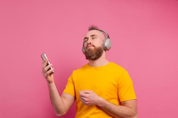 Knappe man in casual dansen met mobiele telefoon en koptelefoon geïsoleerd op roze achtergrond