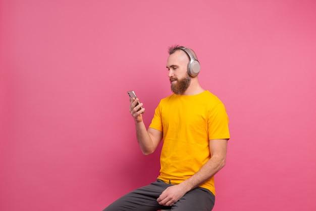 Knappe man in casual luisteren naar muziek met koptelefoon geïsoleerd op roze achtergrond