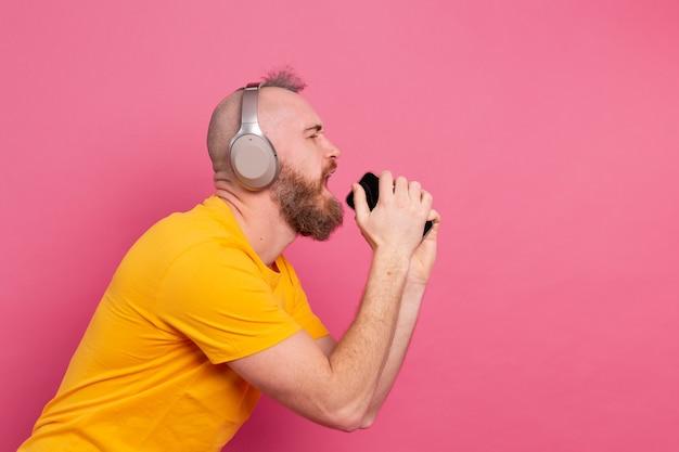 Knappe man in casual zingen met koptelefoon voor mobiele telefoon geïsoleerd op roze achtergrond