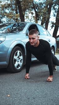 Knappe man in de buurt van de auto. de atleet wrong zich naast de machine uit. auto versus man