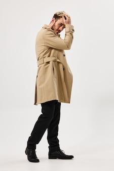 Knappe man in een beige jas aantrekkelijke studio moderne stijl