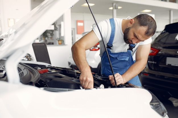 Knappe man in een blauw uniform controleert de auto