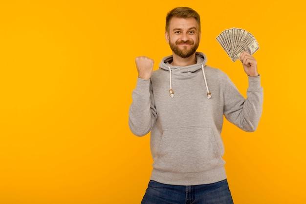 Knappe man in een grijze hoodie geniet van het winnen van de loterijgeld dollars op een gele achtergrond - afbeelding