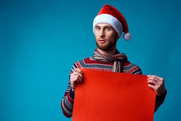 Knappe man in een kerst oranje mockup poster blauwe achtergrond. hoge kwaliteit foto