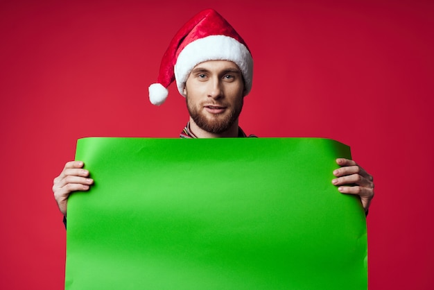 Knappe man in een kerstmuts met groene mockup studio poseren