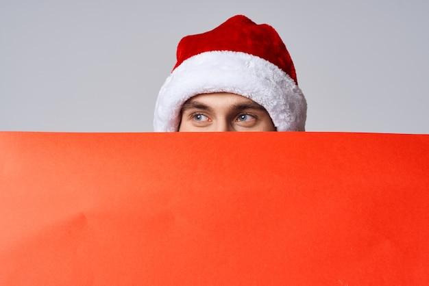 Knappe man in een kerstmuts met rode mockup poster geïsoleerde achtergrond