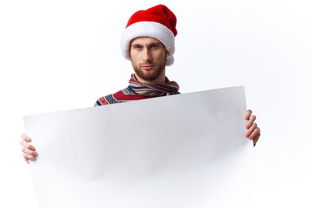 Knappe man in een kerstmuts met witte mockup poster kerst lichte achtergrond