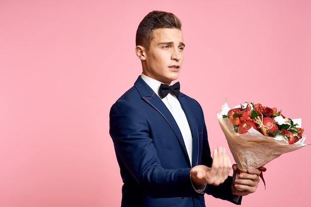 Knappe man in een klassiek pak met een boeket bloemen op een roze achtergrond