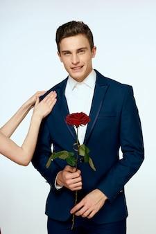 Knappe man in een klassiek pak met een roos in zijn handen