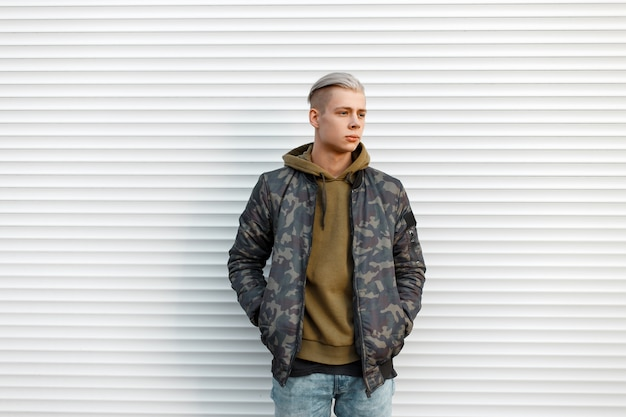 Knappe man in een militair jasje met een sweatshirt in spijkerbroek in de buurt van witte metalen muren