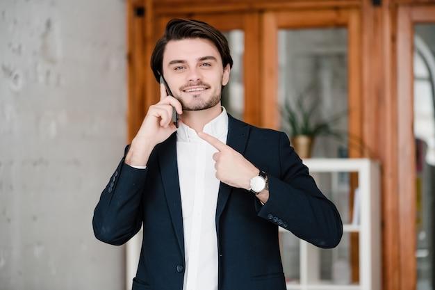 Knappe man in een pak gebruikt telefoon op kantoor