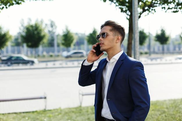 Knappe man in een pak loopt langs de straat in een zonnige dag en praat over zijn smartphone