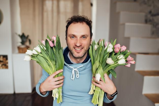 Knappe man in een sweatshirt glimlacht en houdt een boeket tulpen in zijn handen