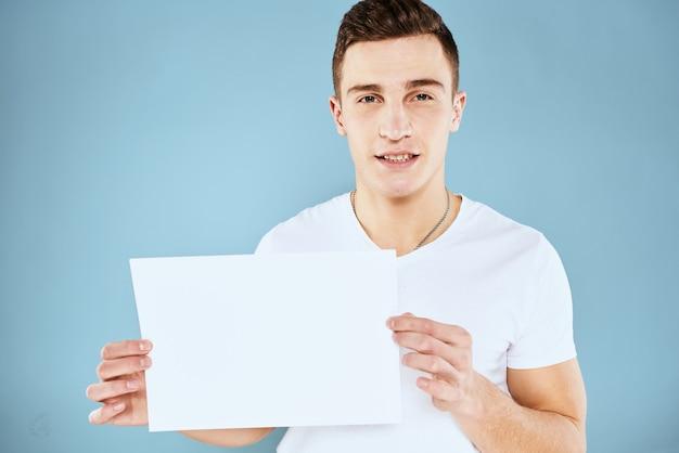Knappe man in een t-shirt houdt een wit vel zonder inscriptie vast