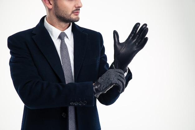 Knappe man in een vest en pet draagt leren handschoenen op donkere muur