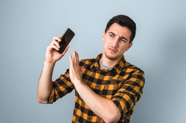 Knappe man in geel overhemd geïrriteerd door iemands stem op telefoon gebarend met zijn hand niet meer zeggend