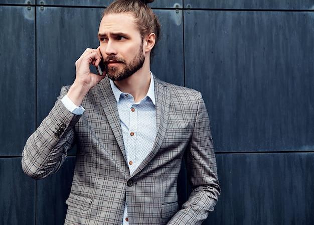 Knappe man in grijs geruit pak spreken met smartphone