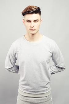 Knappe man in grijs shirt met lange mouwen houdt handen achter zijn rug