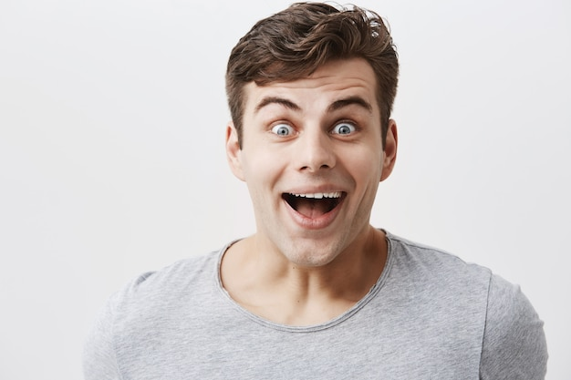 Knappe man in grijs t-shirt, glimlacht van verbazing, kijkt met afgeluisterde blauwe ogen, verbaasd om onverwacht nieuws te horen of cadeau van vriend te zien. positieve emoties en gevoelens concept.