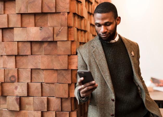 Knappe man in grijze jas zijn telefoon kijken
