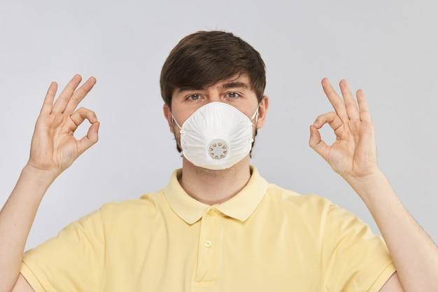 Knappe man in herbruikbaar gasmasker ter bescherming tegen vervuiling en coronavirus met ok handgebaar