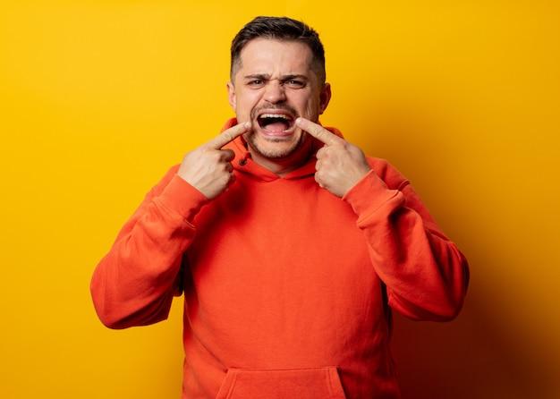 Knappe man in hoodie op gele muur