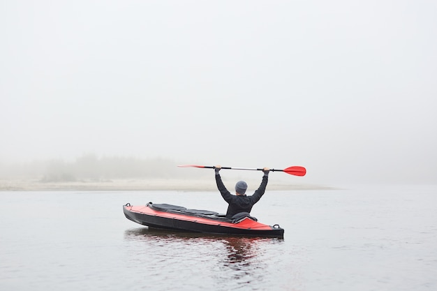 Knappe man in kajak op rivier met opgeheven riem