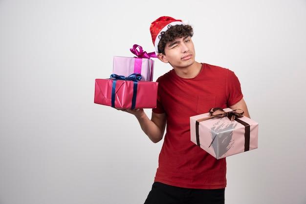Knappe man in kerstmuts luisteren naar geluid van geschenken.