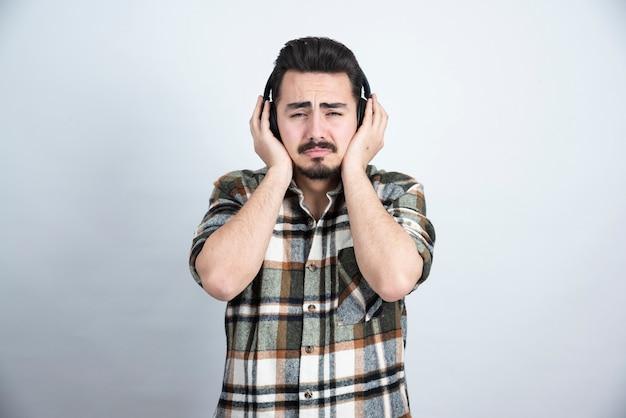Knappe man in koptelefoon huilen op witte muur.