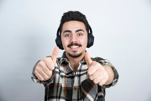 Knappe man in koptelefoon kijken op witte muur.