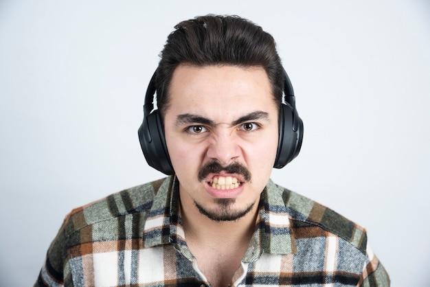 Knappe man in koptelefoon kijkt boos over witte muur.