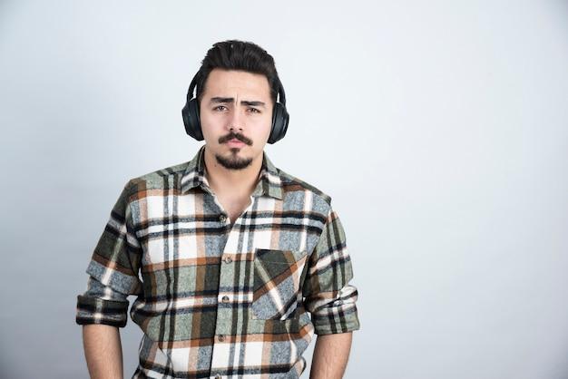 Knappe man in koptelefoon op zoek naar camera over witte muur.