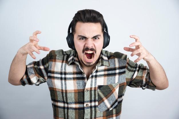 Knappe man in koptelefoon schreeuwen op witte muur.