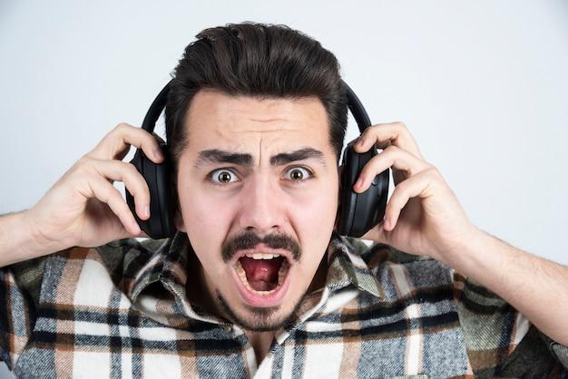 Knappe man in koptelefoon staan en luisteren naar lied.
