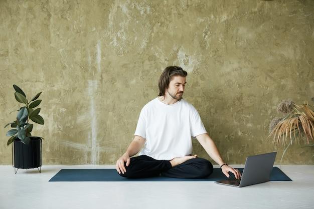 Knappe man in lotus houding met behulp van laptop, mannelijke zittend op yoga mat en typen op computer in wit overhemd, kopieer ruimte