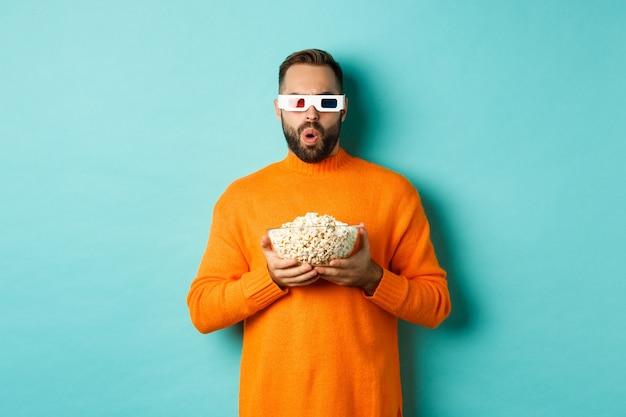 Knappe man in oranje trui en 3d-bril kijken naar films opgewonden, popcorn vasthouden, verbaasd kijken, staande over blauwe achtergrond.