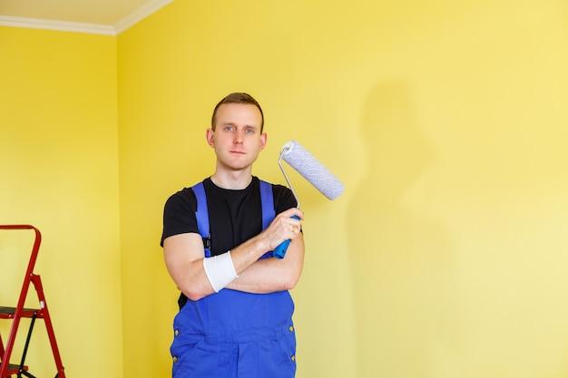 Knappe man in overall houdt verfroller vast. gereedschapsaccessoires voor de renovatie van een appartementkamer. woningrenovatieconcept