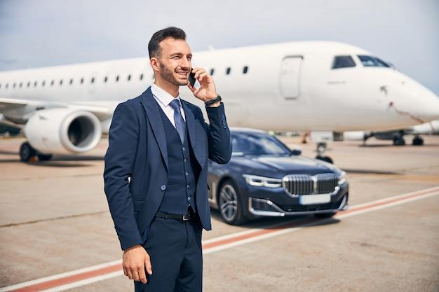 Knappe man in pak aan de telefoon terwijl hij voor een vliegtuig staat