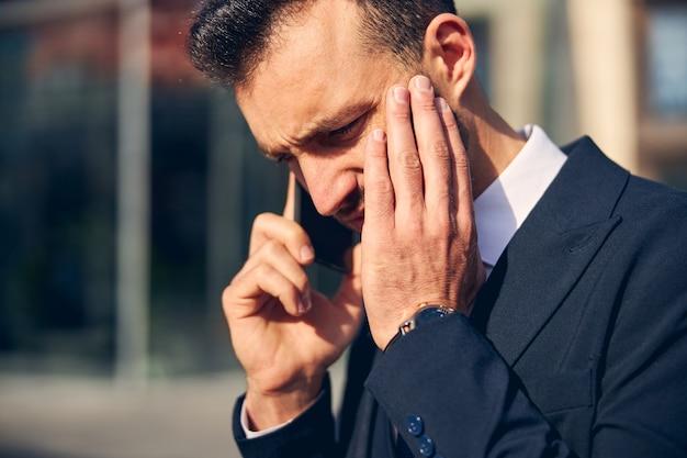 Knappe man in pak die geconcentreerd en serieus kijkt terwijl hij buiten spreekt oh mobiele telefoon phone