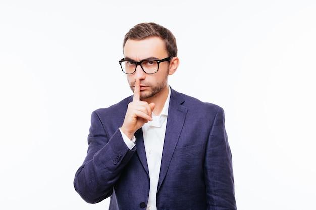 Knappe man in pak doet een stiltegebaar met wijsvinger geïsoleerd op wit