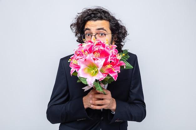 Knappe man in pak met boeket bloemen die er bezorgd uitziet