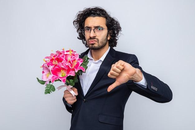 Knappe man in pak met boeket bloemen die er ontevreden uitziet met duimen naar beneden