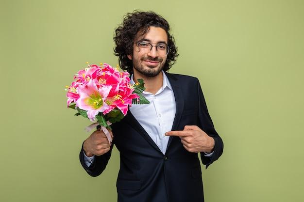 Knappe man in pak met boeket bloemen wijzend met wijsvinger naar glimlachend zelfverzekerd vieren