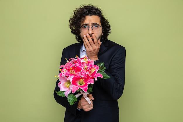 Knappe man in pak met een boeket bloemen die er geschokt uitziet en de mond bedekt met de hand