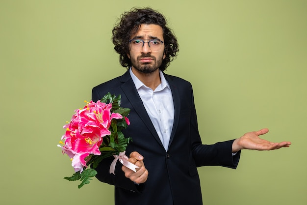 Knappe man in pak met een boeket bloemen die er verward uitziet en zijn arm opsteekt in ongenoegen om te vieren